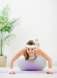 La fabbricazione della donna di forma fisica spinge verso l'alto sulla sfera di forma fisica Immagini Stock
