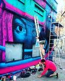 La fabbricazione di una pittura murala di una donna a Londra Fotografia Stock