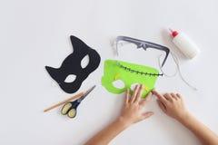 La fabbricazione maschera la maschera di carta del ` s del mostro di Halloween di festa mani del gatto nero vista superiore immagine stock
