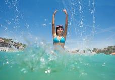 La fabricación adolescente de la muchacha salpica en agua de mar clara Fotografía de archivo