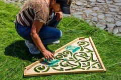 La fabricación del modelo teñido del serrín en aguja del pino prestó la alfombra, Antigua, Foto de archivo