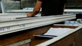 La fabricación y la fabricación de las ventanas del PVC, un trabajador de sexo masculino instala un sello de goma en un marco del almacen de video