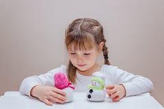 La fabrication de petite fille handcraft le bonhomme de neige Photographie stock libre de droits
