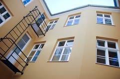 La facciata beige leggera della casa con le grandi finestre e un abete fotografia stock