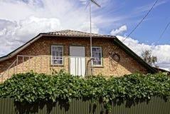 La facciata della casa con un balcone del ferro e un recinto invaso Fotografia Stock Libera da Diritti