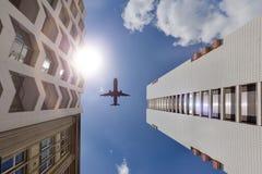 La facciata di alta costruzione con un aeroplano nel cielo blu Immagini Stock Libere da Diritti