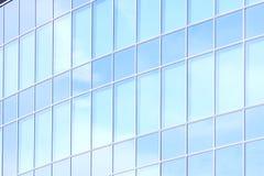 La facciata di vetro di un grattacielo con una riflessione di specchio delle finestre del cielo Immagini Stock