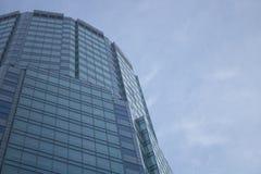 La facciata di vetro di un grattacielo con una riflessione di specchio delle finestre del cielo Fotografie Stock