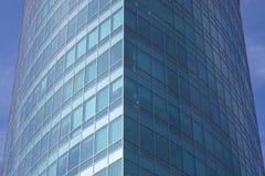 La facciata di vetro di un grattacielo con una riflessione di specchio delle finestre del cielo Immagine Stock