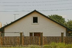 La facciata grigia di una casa con le finestre dietro un di legno recinta l'erba Immagine Stock