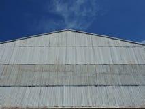 La facciata ondulata dello zinco sale in cielo blu fotografia stock libera da diritti