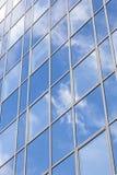 La fachada de cristal de la oficina refleja las nubes y el cielo azul fotos de archivo