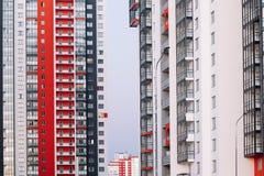 La fachada de un edificio alto con las rayas blancas y grises rojas Edificio de varios pisos contra el cielo azul Fondo a fotos de archivo libres de regalías