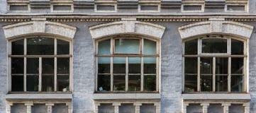 La fachada gris de un edificio histórico con tres arqueó ventanas Imágenes de archivo libres de regalías