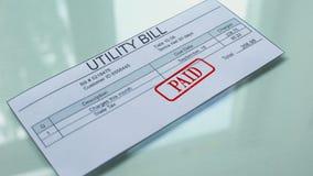 La factura de servicios públicos pagó, mano que sellaba el sello en el documento, pago para los servicios, tarifa metrajes