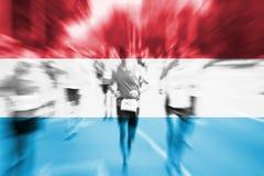 La falta de definición de movimiento del corredor de maratón con la mezcla de Luxemburgo señala por medio de una bandera Imagen de archivo libre de regalías