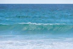 La falta de definición del fondo y la onda potente se rompe a lo largo de la orilla imagenes de archivo