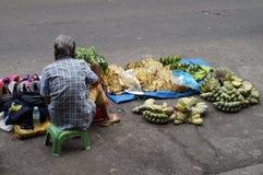 La falta de instalaciones del mercado hace a esta mujer vender plátanos y calzados a lo largo de la calle de la ciudad imagen de archivo libre de regalías