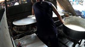 La falta de instalaciones del mercado hace a este hombre cocer la envoltura vegetal de la harina en el lado de la calle almacen de video