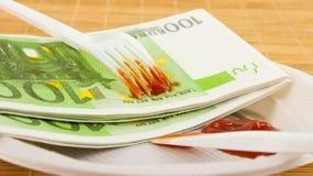 La fame per soldi, 100 tovaglioli degli euro, ketchup, la forcella di plastica ed il coltello Fotografia Stock