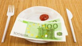 La fame per soldi, 100 tovaglioli degli euro, ketchup, la forcella di plastica ed il coltello Fotografie Stock