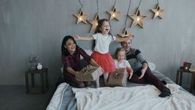 La famiglia affascinante sta divertendosi sulla notte di Natale nella camera da letto sul letto Ragazza in una gonna rossa che sa stock footage
