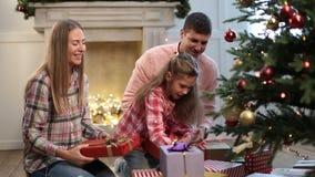 La famiglia allegra che scambia i regali si avvicina all'albero di natale archivi video