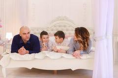 La famiglia amichevole chiacchiera la menzogne sul letto, sulla mamma e sul papà con il loro bambino Immagine Stock