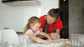 La famiglia amorosa felice sta preparando insieme il forno La ragazza della figlia del bambino e della madre sta cucinando i bisc archivi video