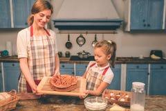 La famiglia amorosa felice sta preparando insieme il forno Ragazza della figlia del bambino e della madre divertendosi nella cuci fotografia stock