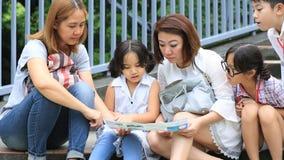 La famiglia asiatica felice smette di esaminare insieme la mappa della traccia , All'aperto nel parco stock footage