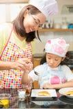 La famiglia asiatica gode di di produrre il pancake, madre asiatica e la figlia gode di di fare il forno Immagine Stock