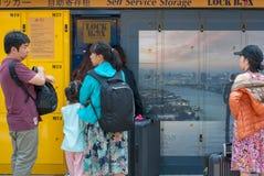La famiglia asiatica sta stando davanti allo stoccaggio giallo di self service immagine stock