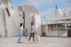 La famiglia cammina con un cane fotografia stock