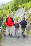 La famiglia cammina sulla strada della montagna Fotografie Stock