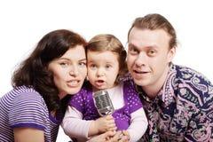 La famiglia canta nel microfono immagine stock libera da diritti