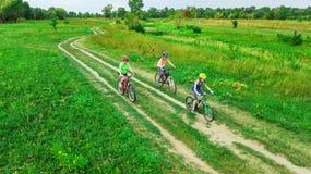 La famiglia che cicla sulla vista aerea delle bici all'aperto da sopra, madre attiva con i bambini si diverte, sport della famigl Fotografie Stock