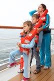 La famiglia che porta in giubbotti di salvataggio si leva in piedi alla piattaforma Fotografie Stock Libere da Diritti