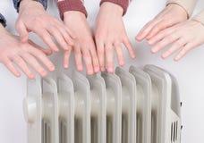 La famiglia che riscalda cosegna il riscaldatore elettrico immagini stock libere da diritti