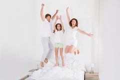 La famiglia che salta insieme sul letto Fotografie Stock Libere da Diritti