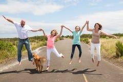La famiglia che salta insieme sulla strada Fotografie Stock Libere da Diritti