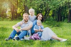 La famiglia con due bambini riposa nel giardino dell'estate Immagine Stock