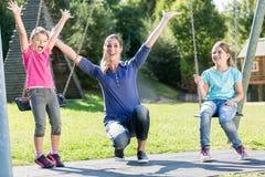 La famiglia con due ragazze e la madre sul campo da giuoco oscillano Fotografia Stock