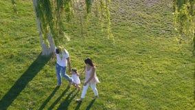 La famiglia con il bambino cammina su erba verde video d archivio