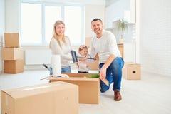 La famiglia con il bambino si muove verso una nuova casa immagini stock