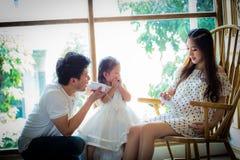 La famiglia con la bambina in giocatori può telefonare Immagini Stock