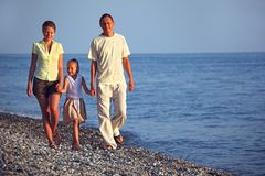 La famiglia con la ragazza cammina lungo la spiaggia del mare di tramonto Fotografia Stock