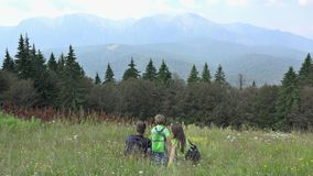 La famiglia con lo zaino che riposa sull'erba ed ammira la natura stock footage