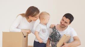 La famiglia con un ragazzino disimballa le scatole di cartone con le decorazioni di Natale stock footage