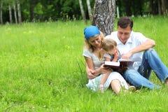 La famiglia con una giovane figlia legge la bibbia Immagine Stock